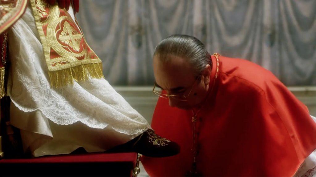 Pie XIII, dans The Young Pope, est un tyran qui humilie ses conseillers, comme ici le cardinal Voiello (Silvio Orlando) en l'obligeant à baiser son pied, devant tous les autres cardinaux...